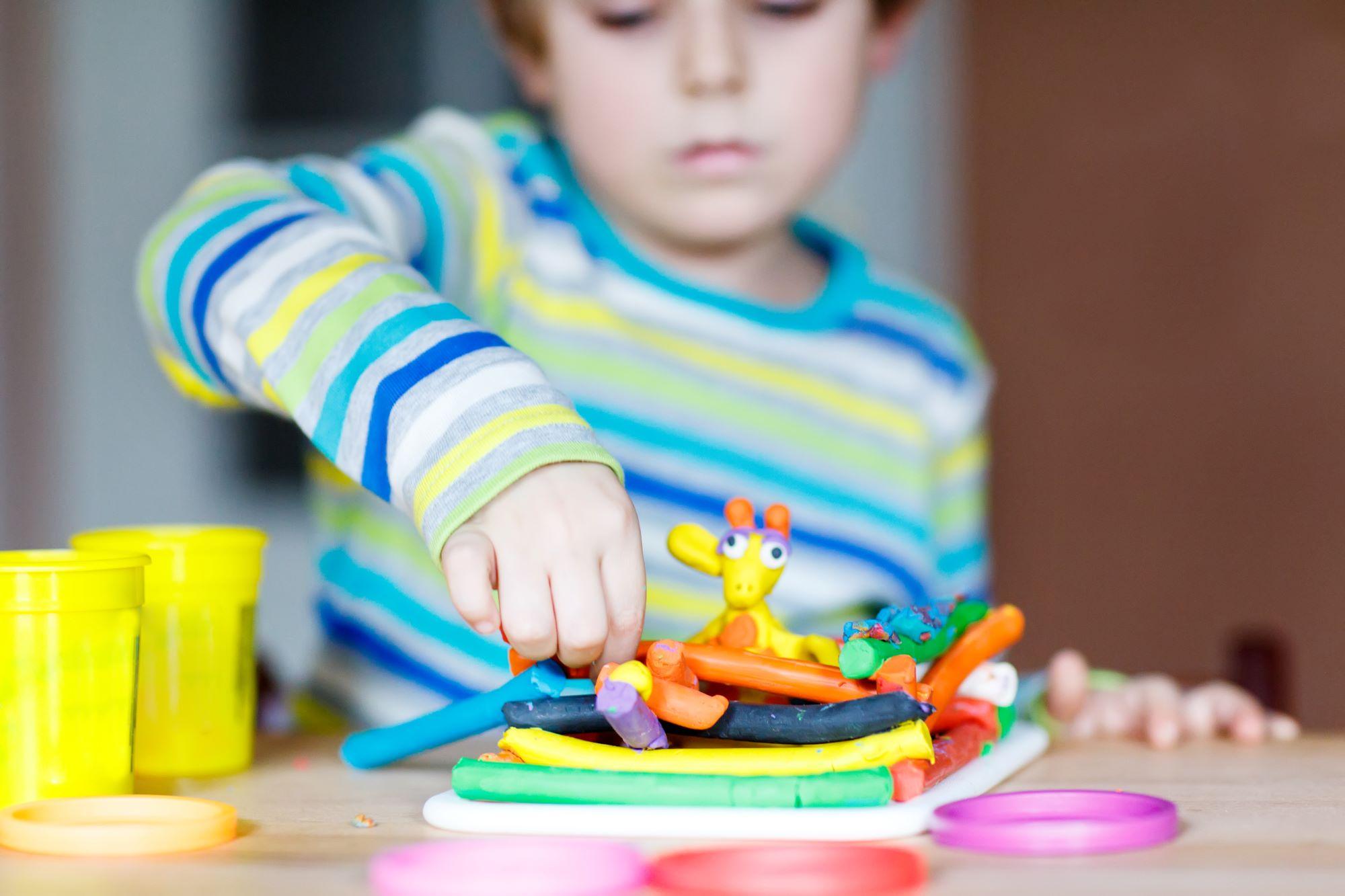Lapsi leikkii pöydän ääressä.